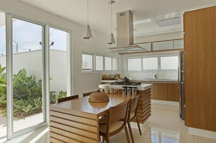 Cozinha planejada com ilha e mesa de madeira.