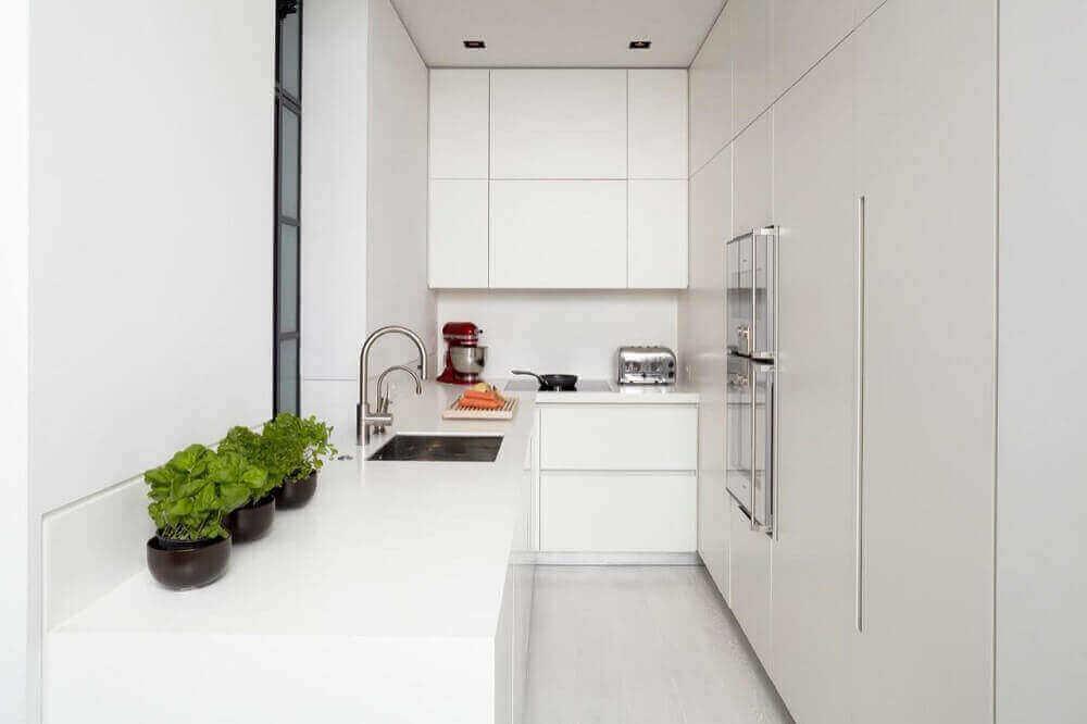 Apartamento pequeno com armários brancos.
