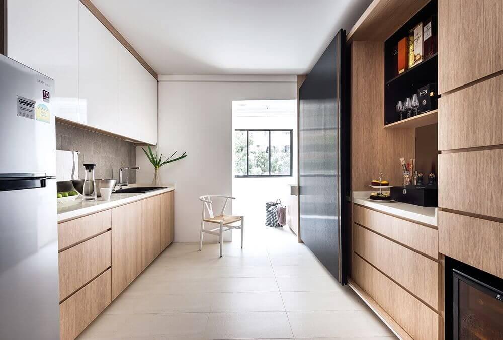 Cozinha planejada moderna com armário de madeira e porta deslizante.