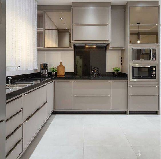 Cozinha planejada com armários espelhados e cinza.