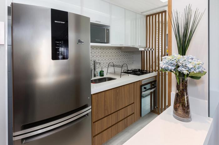 Cozinha planejada pequena com armário de madeira.