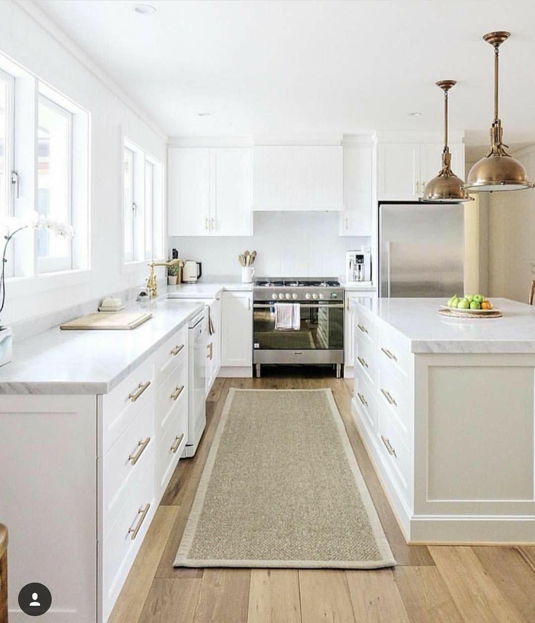 Cozinha planejado com ilha e armários brancos.