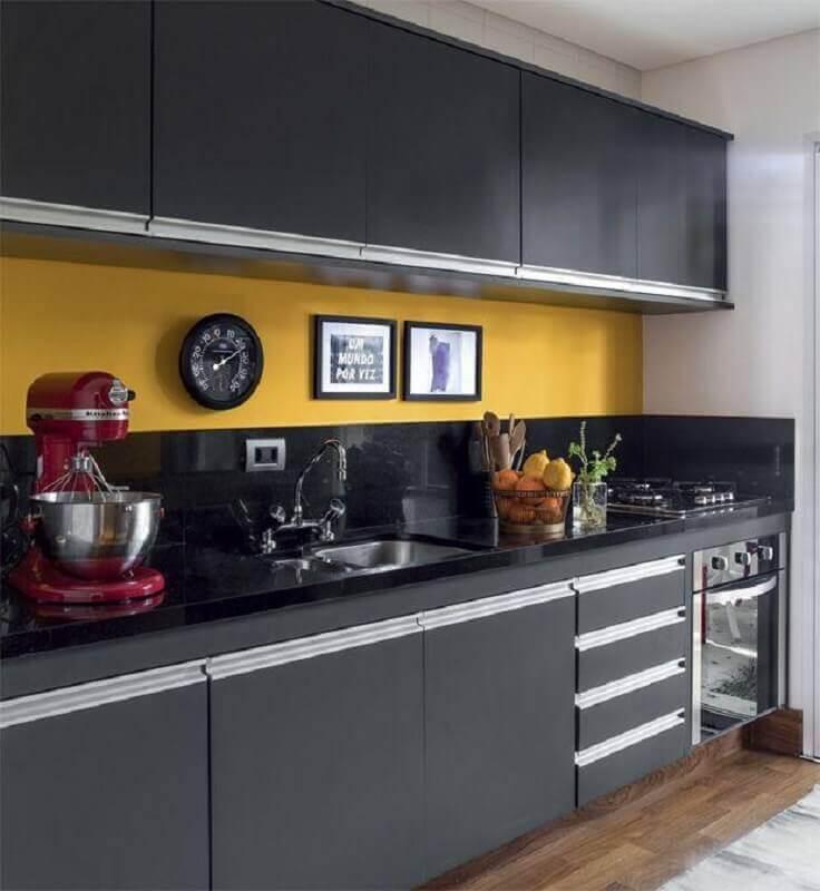 Cozinha planejada com decoração amarela e armário preto.