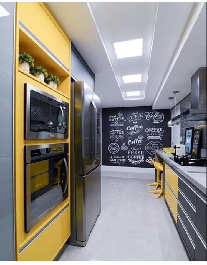 Cozinha planejado com tinta de lousa e armários amarelos.