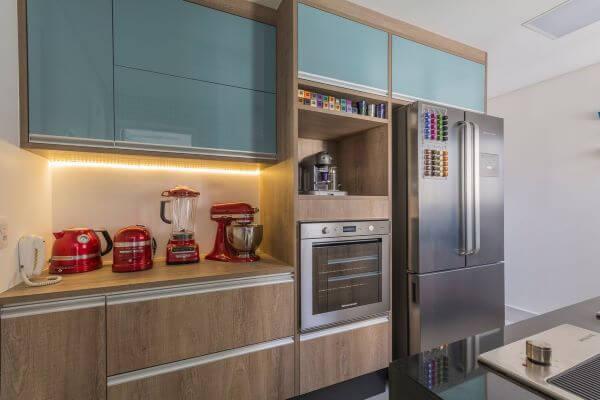 Cozinha planejada pequena com armários azuis.