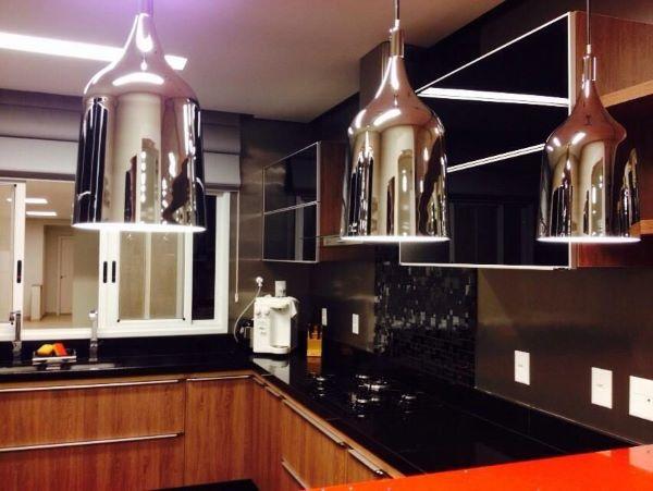 Cozinha planejada com bancada de granito preto.