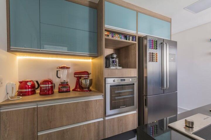 Cozinha planejada pequena com armários azuis e com acabamento de madeira.