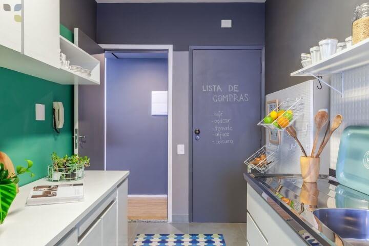 Decoração com armários brancos e parede azul.