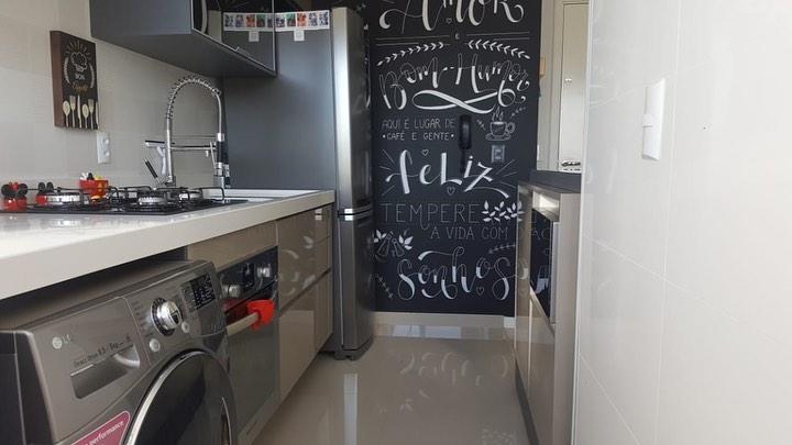 Decoração com armários neutros e parede com tinta de lousa.