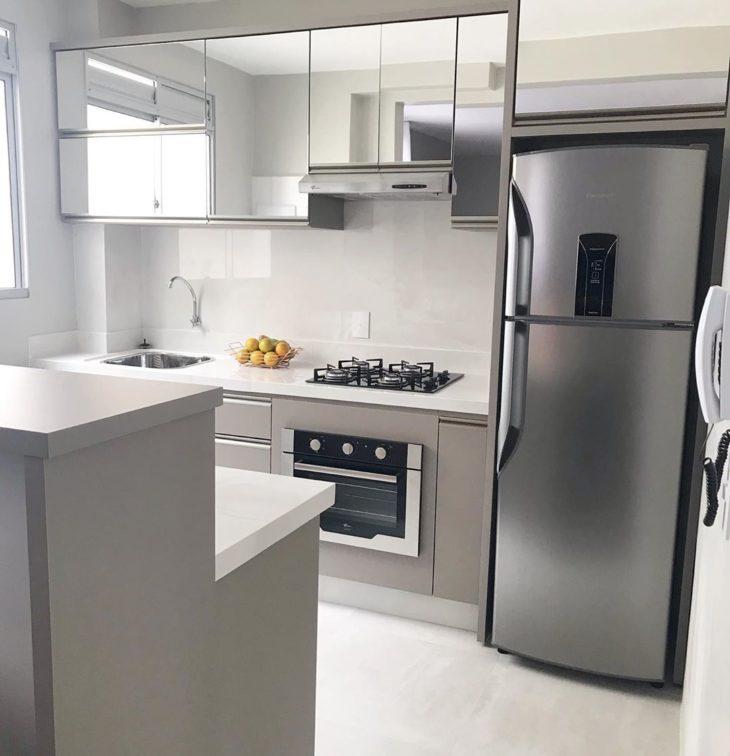 Cozinha pequena com armários espelhados.