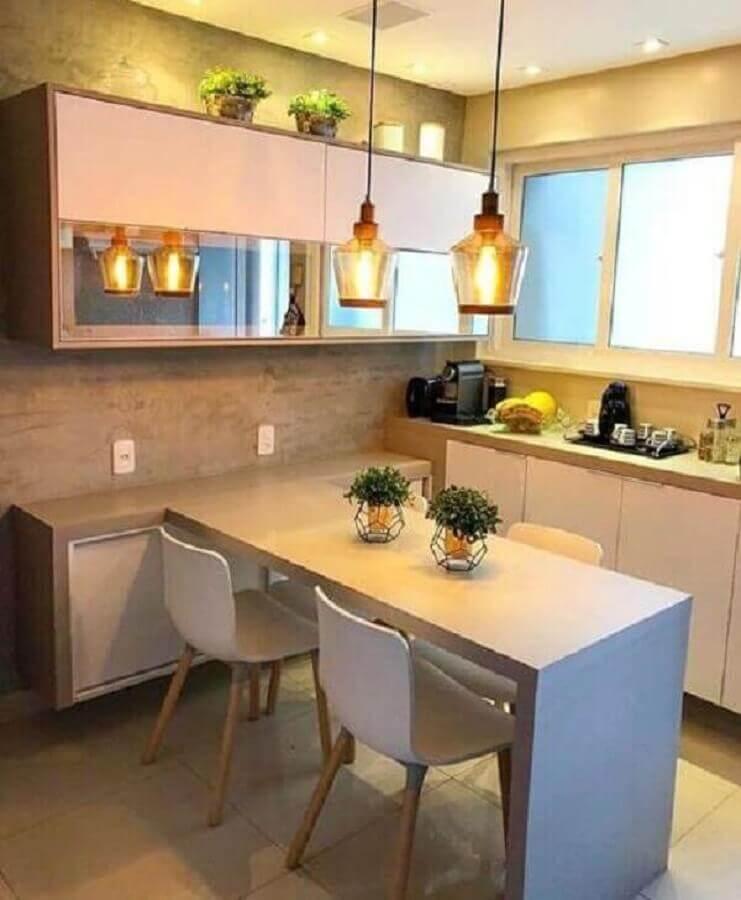 Cozinha planejada pequena com armários brancos e parede de cimento queimado.