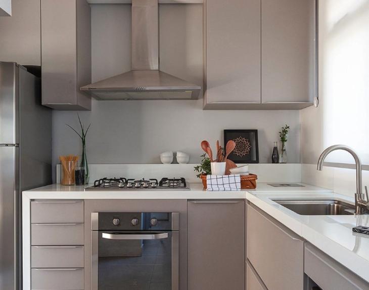 Cozinha pequena com armários neutros e bancada branca.