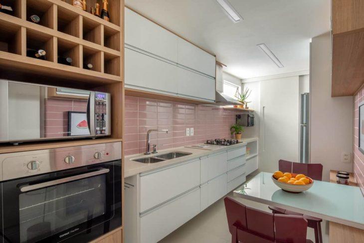 Cozinha planejada pequena com azulejo rosa.