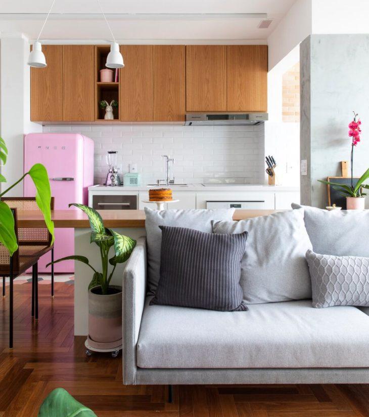 Decoração com armários de madeira e geladeira vintage rosa.