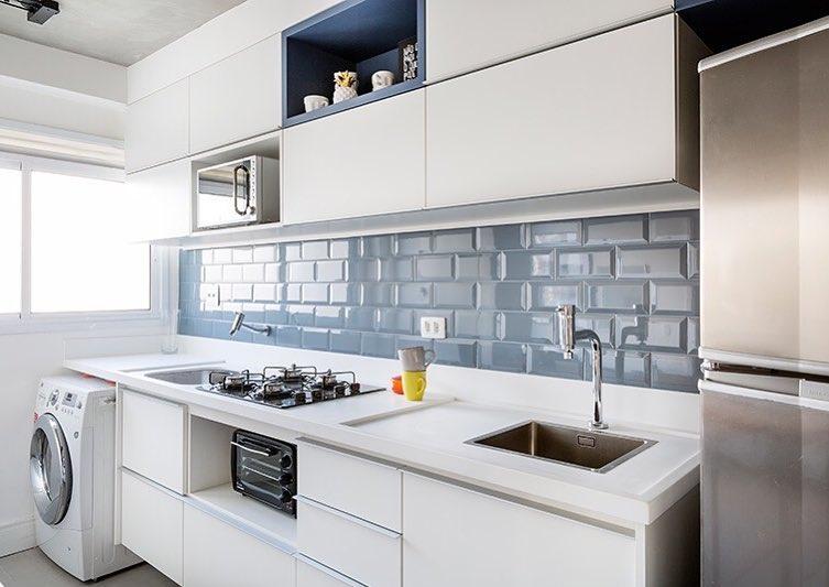 Decoração com armários brancos e azulejos azuis.