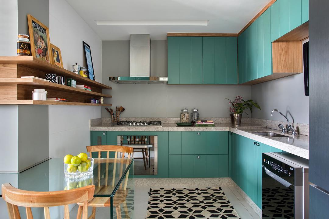 Cozinha pequena com armário verde e bancada de vidro.