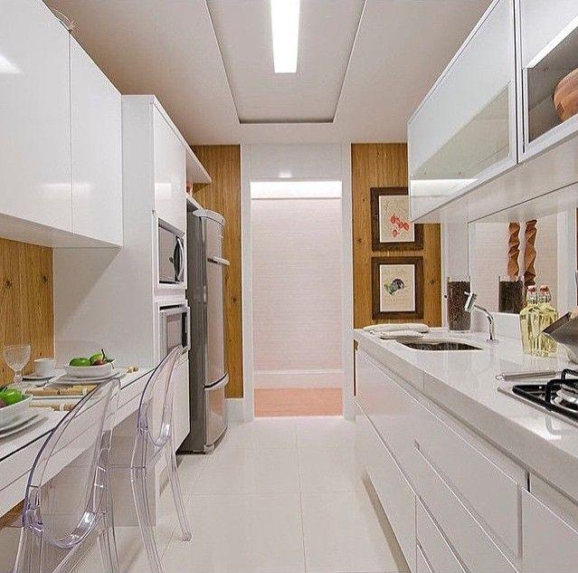 Cozinha planejada pequena com bancada branca de madeira.