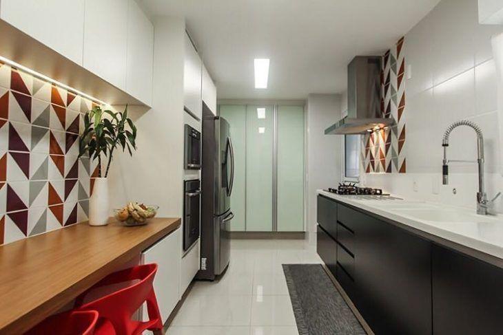 Decoração com armários pretos, azulejos coloridos e bancada de madeira.