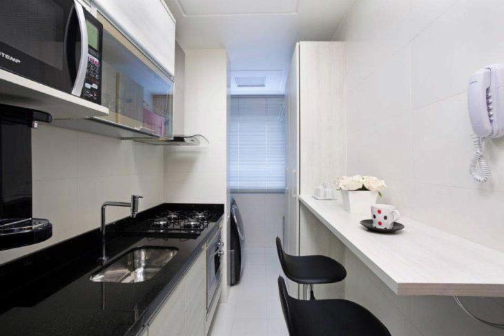 Cozinha pequena com bancada de madeira.