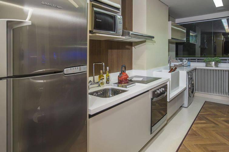Cozinha planejada pequena com armários em tons neutros.