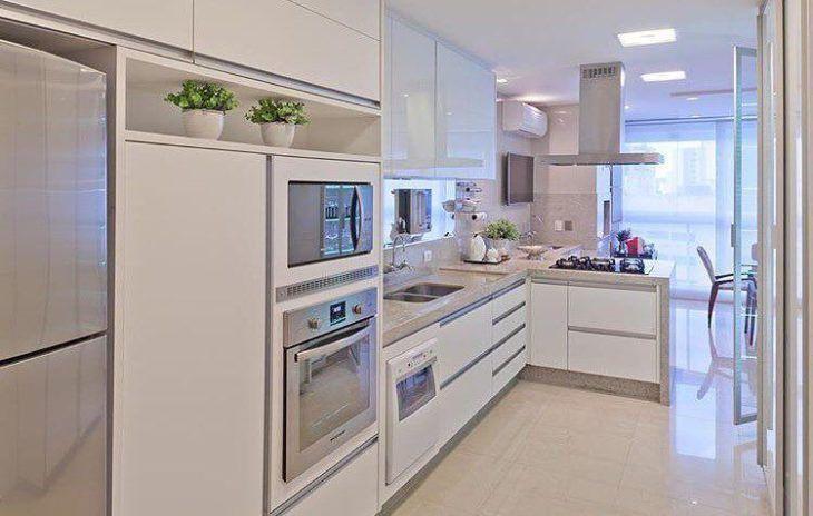 Cozinha planejada pequena com armários brancos e simples.,