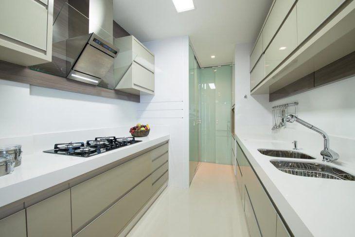 Cozinha planejada pequena com armários de tons neutros.