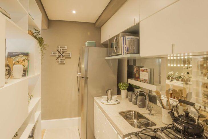 Cozinha planejada pequena com armários brancos e estante com nichos.