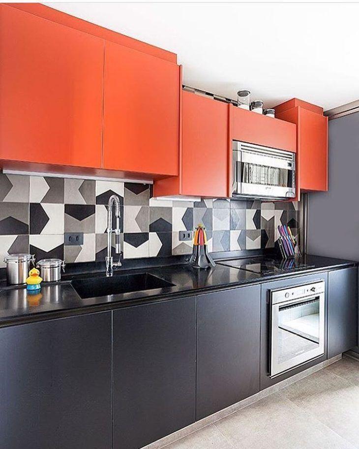 Decoração com armário preto e laranja e azulejo decorado.