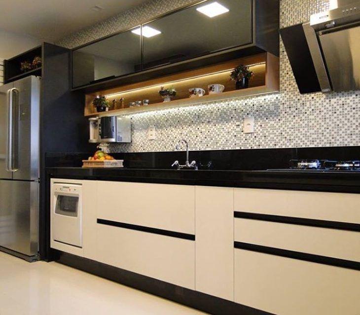 Cozinha moderna com armários pretos e pastilhas de cerâmico.
