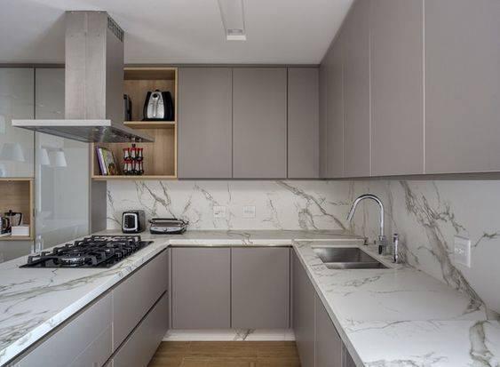 Decoração moderna com armários cinzas e bancada de mármore.