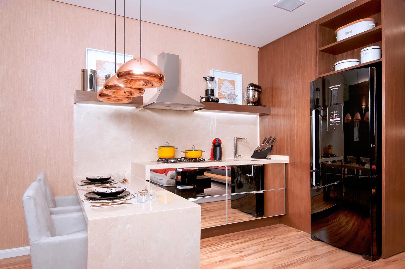 Cozinha planejada pequena com armários espelhados e geladeira preta.
