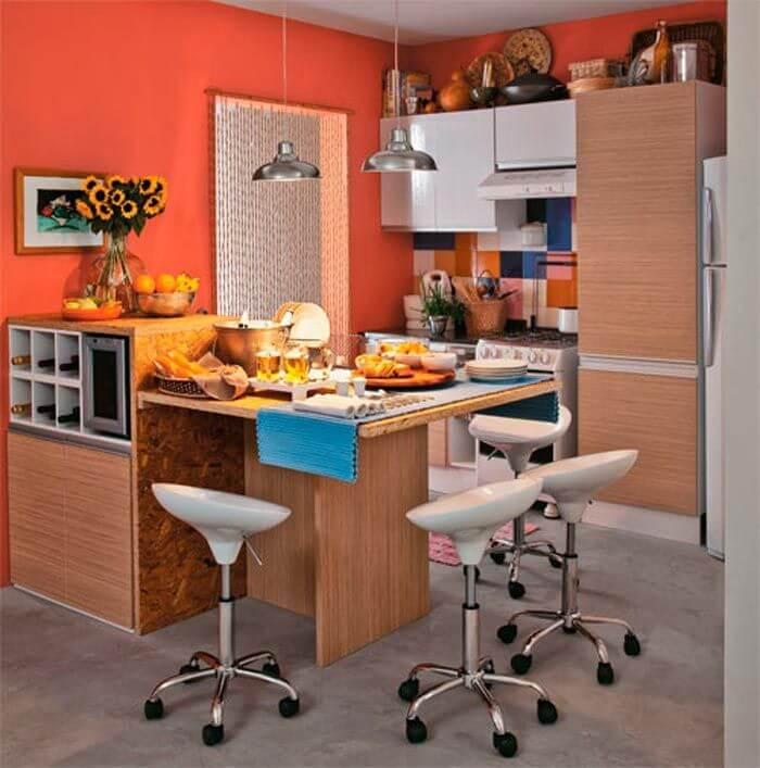 Cozinha planejada pequena com parede laranja.