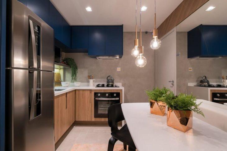 Decoração moderna com espelho, armários azuis e parede de cimento queimado.