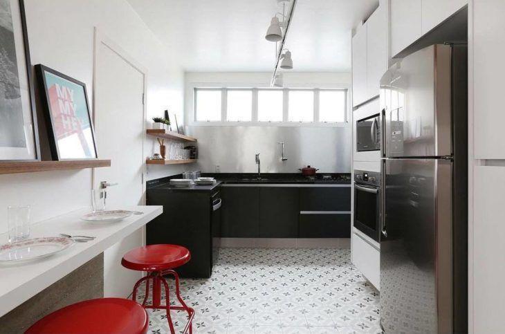 Decoração com armários pretos e bancada branca de madeira.