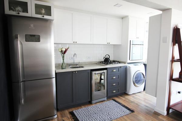 Cozinha planejada pequena com armário branco e preto.