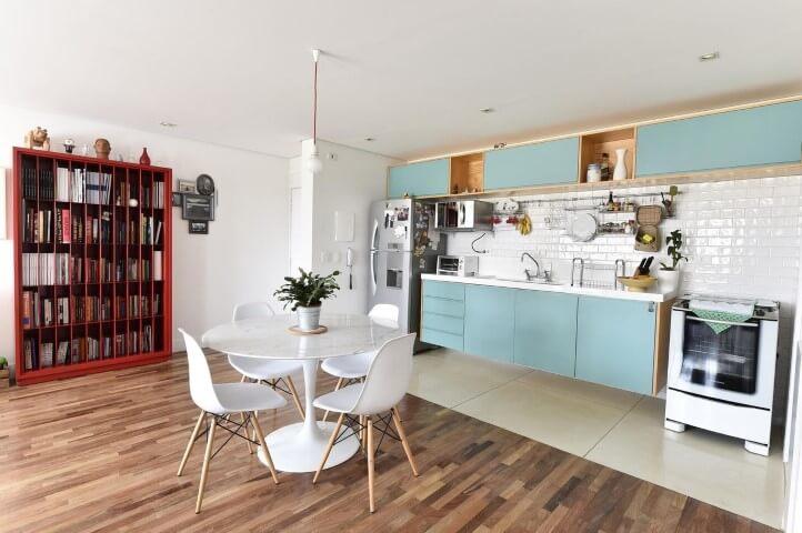 Loft com armários simples azuis e azulejo de tijolinho branco.