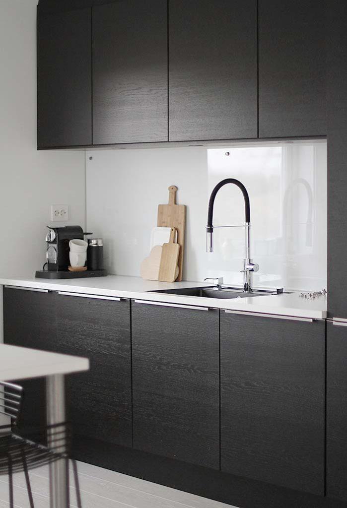 cozinha preta e branca com torneira de bica alta
