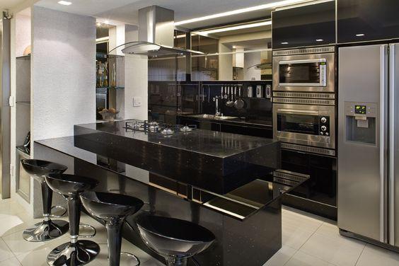 cozinha preta com utensílios e eletros em inox