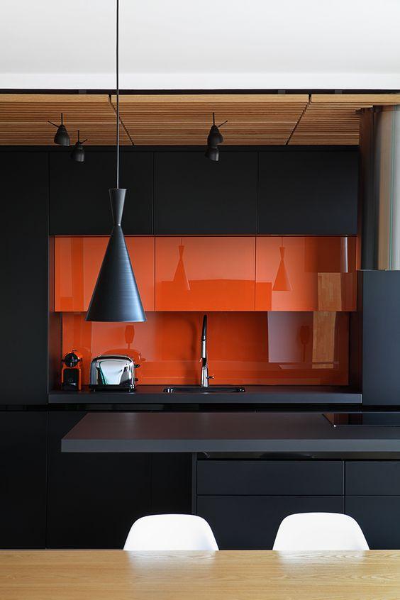 cozinha preta com laranja e pendente moderno