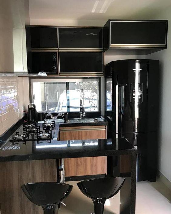 cozinha pequena com geladeira preta