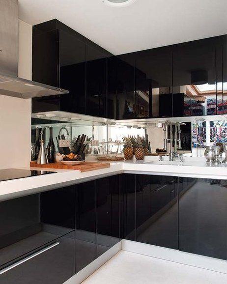 cozinha planejada preta em laca com bancadas brancas e coifa em inos