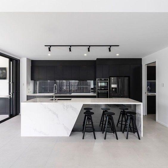 cozinha preta com ilha quartzo branco e geladeira preta