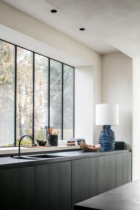 cozinha preta e branca com janela grande e torneira grande