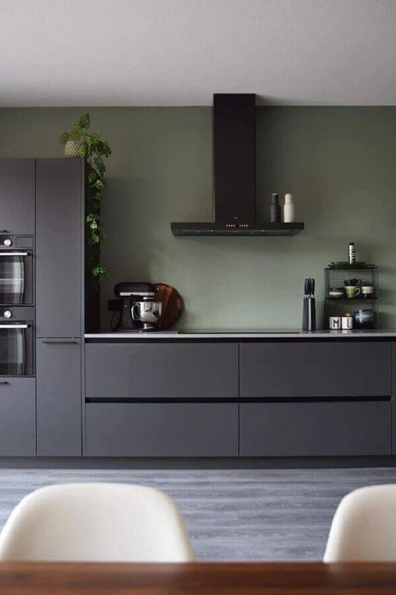 cozinha cinza com detalhes e coifa perta, parede verde