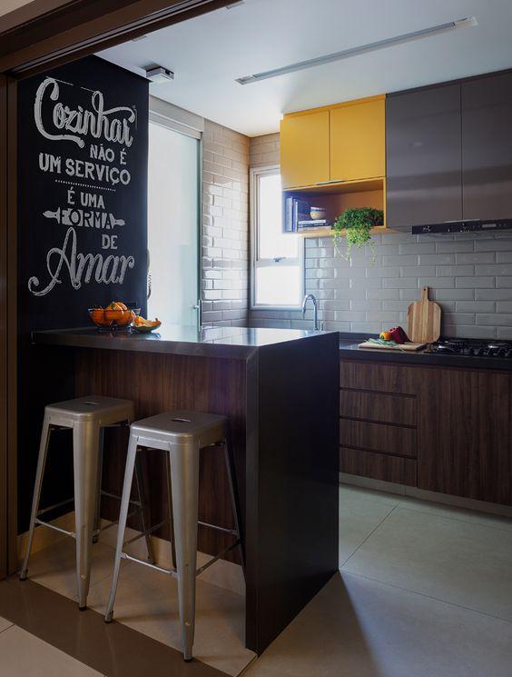 cozinha amarela com parede lousa preta e madeira