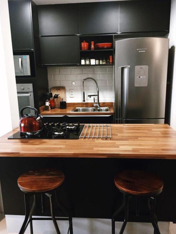 cozinha preta com  bancadas de madeira