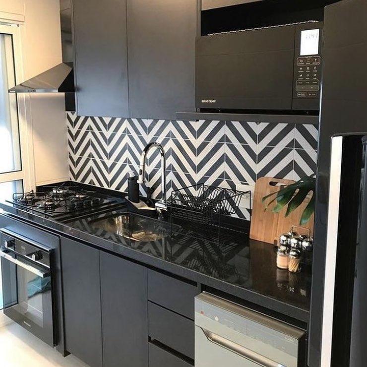 cozinha com azulejo geomátrico preto e branco com armário preto