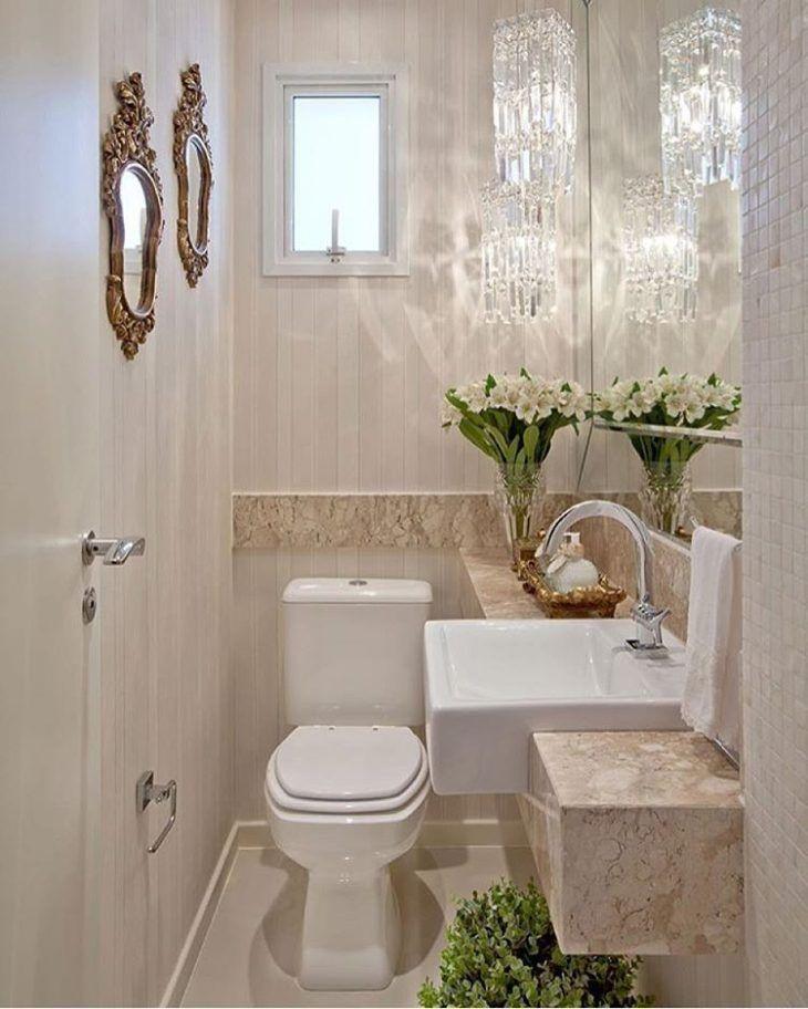 Decoração de apartamento pequeno com lustres de cristais, espelhos e flores em lavabo.