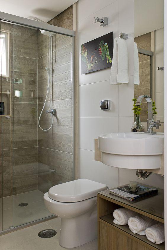 Decoração de banheiro com quadro, pequeno vaso de planta e prateleira com toalhas expostas.