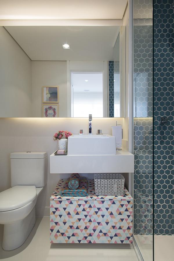Decoração de apartamento pequeno com baú colorido em banheiro e revestimento em azul dentro do box.